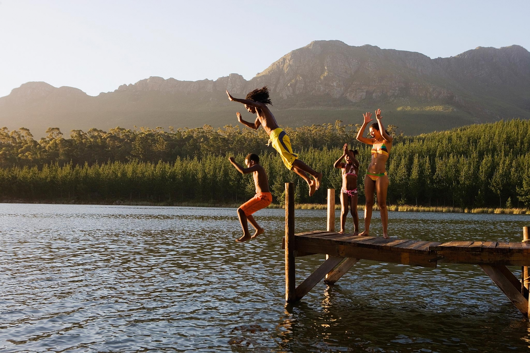 Family jumping in lake